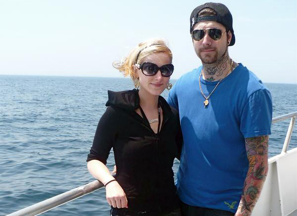 Two people, Alexis Fallon Smith in a black top, and Banksy in a blue t-shirt, stand together at the bow of a boat. They face the camera with an expanse of ocean behind them.