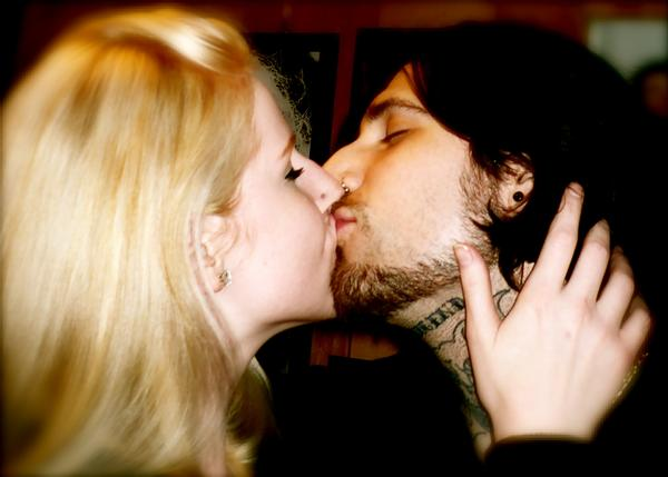 Alexis Smith, with flowing blonde hair, and Banksy with black hair and tattoos on his neck, face each other and kiss, Alexis has a hand on Banksy's neck