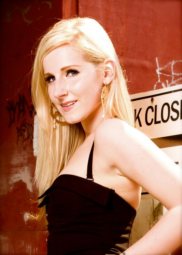 Alexis F. Smith in a waist-length portrait. Fair skin and blonde hair contrasting with a black strappy dress against a deep red wall