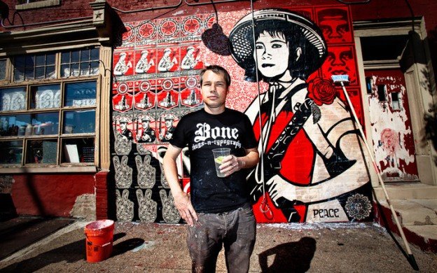 Shepard Fairey standing in front of a just-wheat-pasted mural on the side of the Rock Cat Cafe building in Philadelphia. The iconic black, white, and red poster imagery features his familiar imagery and a very large image of an Asian woman with a hat and a machine gun with a flower blooming out of the bun barrel, a al Bernie Boston