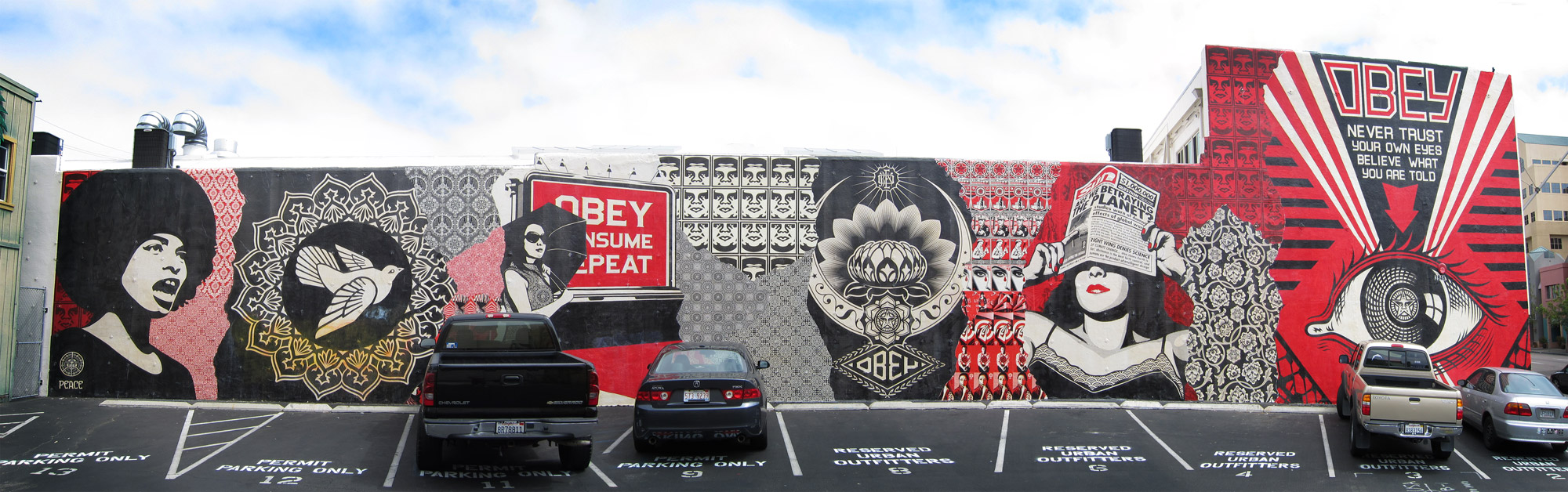 long, parking lot width Shepard Fairey mural in San Diego California featuring Angela Davis, Obey, Global Warming, the All-Seeing-Eye, and other iconic Fairey images